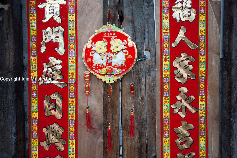 Chinese New Year decorations on very old wooden house door
