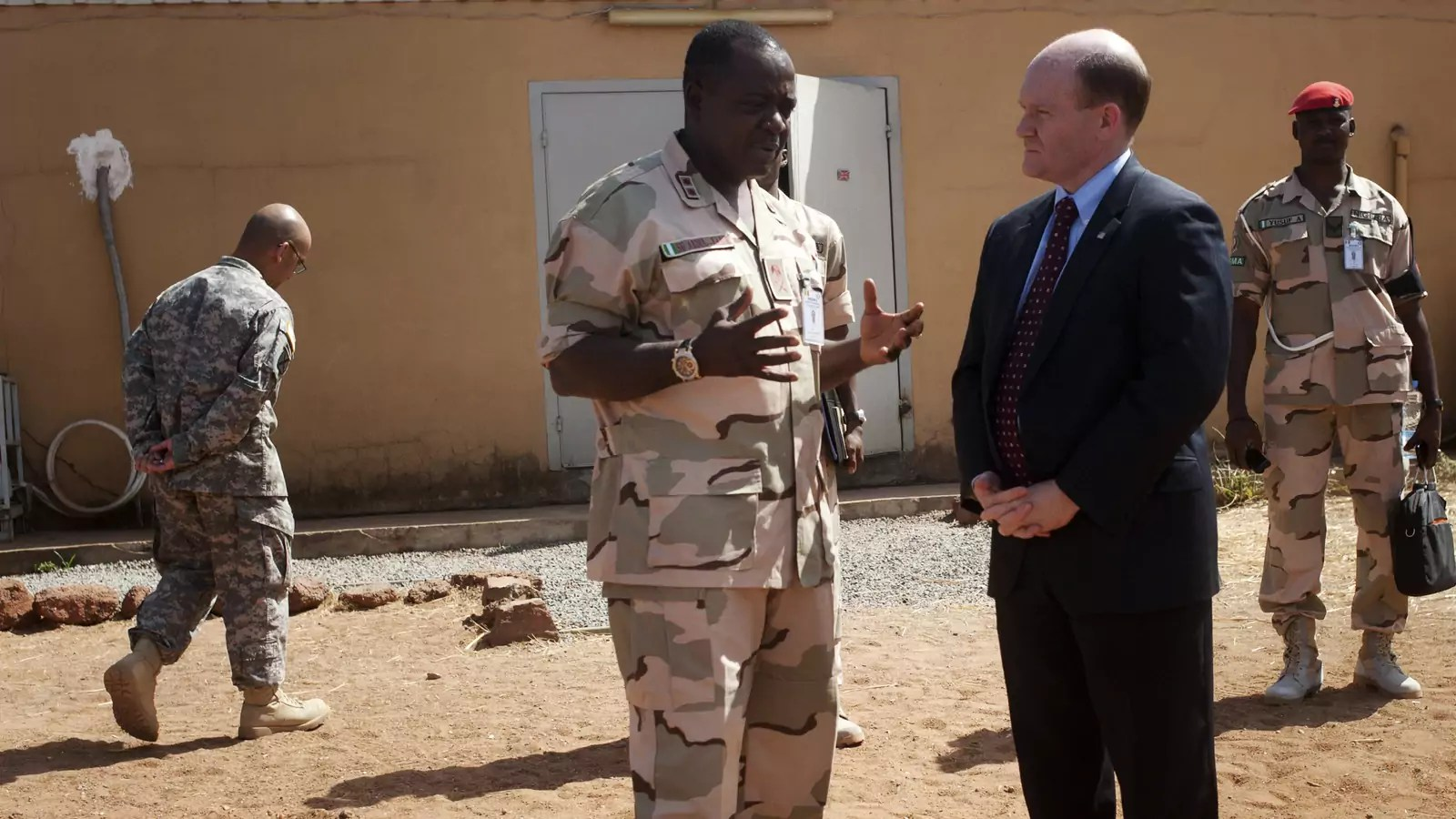 U.S. Senator Chris Coons (C) chats with Force Commander Major General Shehu Abdulkadir on a previous CODEL during President Obama's administration, in Bamako, Mali, February 18, 2013.