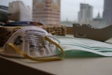 A P2/N95 mask and a surgical mask are placed on a desk in front of a window with a city skyline view.