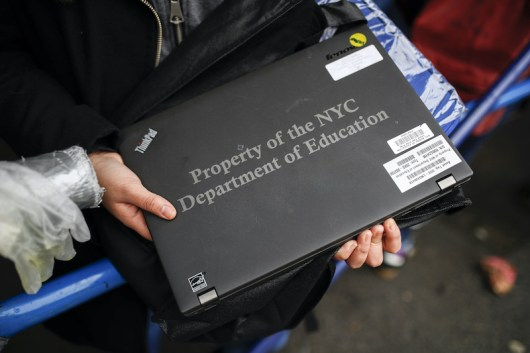 A photo of a hand holding a black laptop labelled Property of NYC Department of Education.