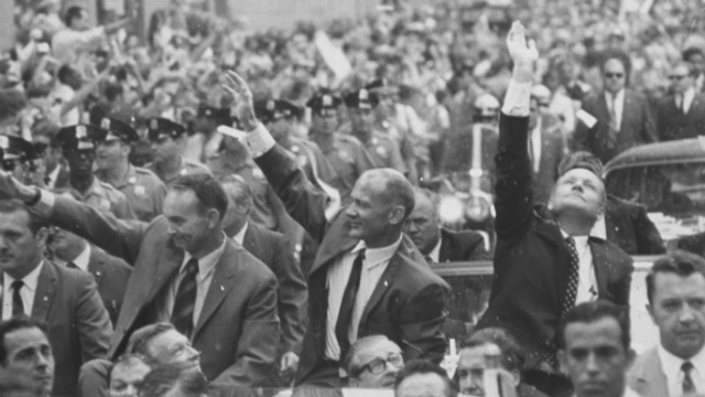 Apollo 11 astronauts Neil Armstrong, Buzz Aldrin and Michael Collins waving to crowds at a parade celebrating their return from the moon.