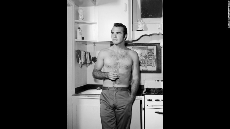 A bare-chested Reynolds stands on a kitchen set in 1960.