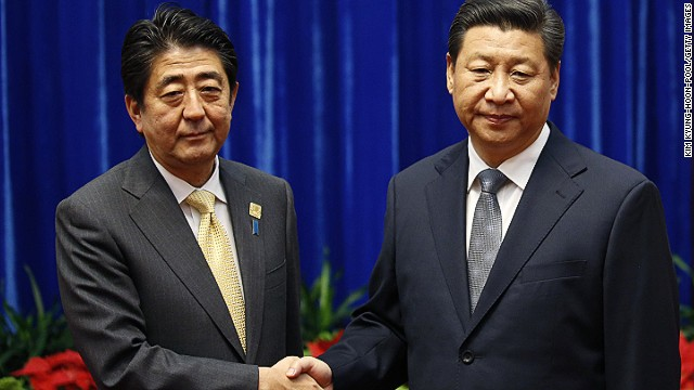 China's President Xi Jinping (R) shakes hands with Japan's Prime Minister Shinzo Abe in Beijing, 2014.