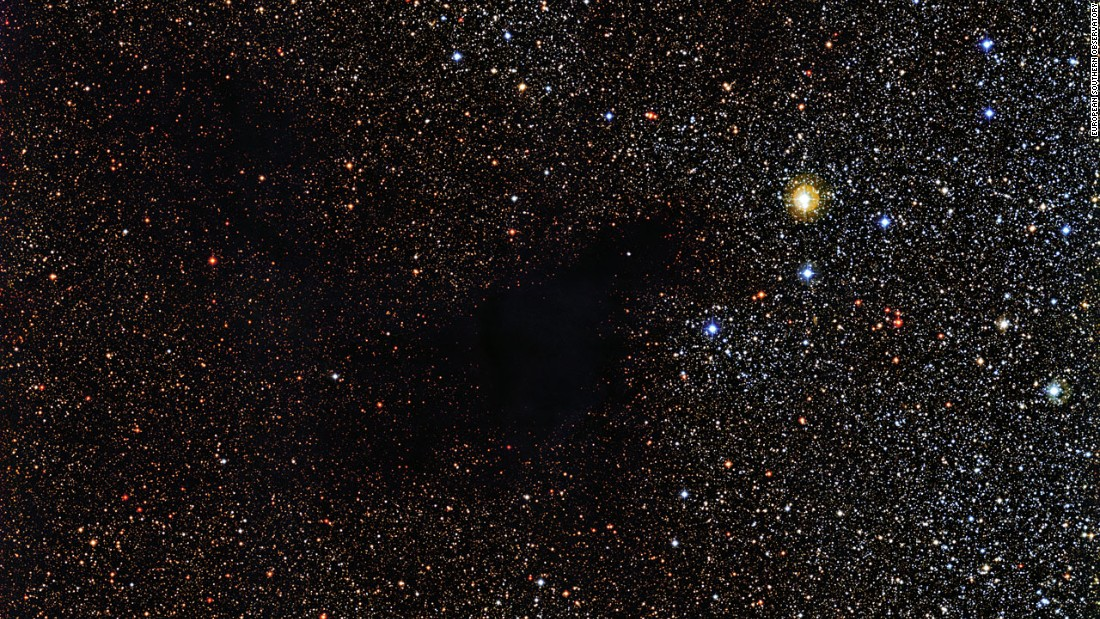 A patch of stars appears to be missing in this image from the La Silla Observatory in Chile. But the stars are actually still there behind a cloud of gas and dust called Lynds Dark Nebula 483. The cloud is about 700 light years from Earth in the constellation Serpens (The Serpent).