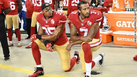 Colin Kaepernick, right, and Eric Reid of the San Francisco 49ers kneel in protest during the National Anthem before playing the Los Angeles Rams on September 12, 2016.