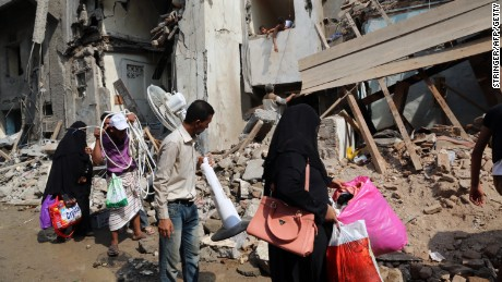 Yemenis carry belongings they recovered from the rubble of buildings destroyed during Saudi-led air strikes in 2016
