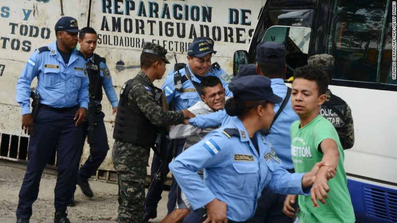 """Police hold a boy whose father was killed in 2016 by alleged gang members for refusing to pay them a """"war tax"""" in Tegucigalpa, Honduras."""