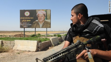 Peshmerga fighter looks at a billboard of Kurdish Regional President Masoud Barzani