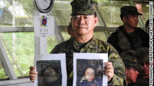 Philippine military chief General Eduardo Ano shows images of militant leaders Isnilon Hapilon and Omar Maute.
