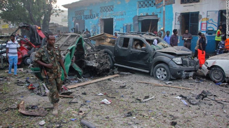 A Somali soldier is shown near wreckage from a car bomb detonated in Mogadishu, Somalia, on Saturday.