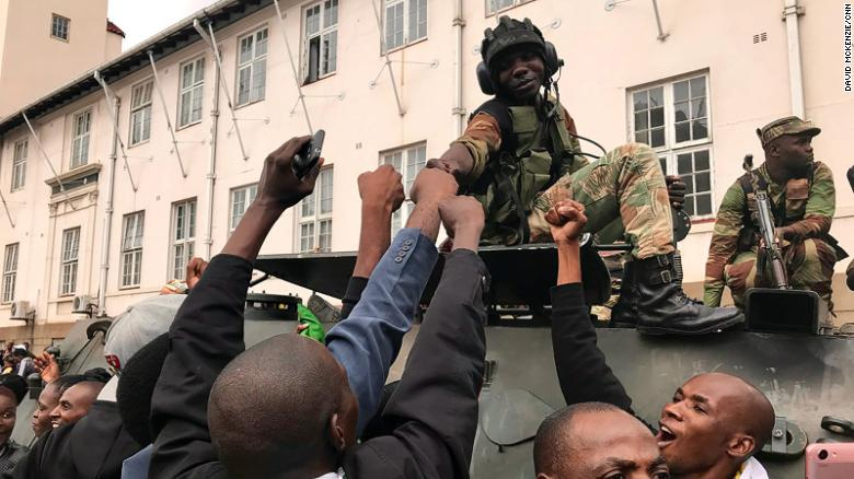 A soldier greets protesters in Harare on Saturday.