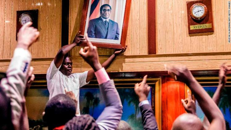 People remove a portrait of former President Mugabe.