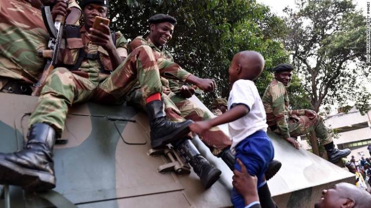 Zimbabweans celebrate outside Parliament; soldiers hoist a child up onto their tank following the announcement.
