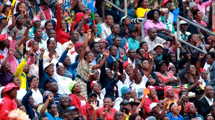 The crowd cheers and dances at the inauguration ceremony in Harare on Friday.