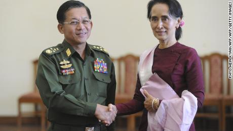 Senior General Min Aung Hlaing, Myanmar Commander In-Chief (L) and National League for Democracy (NLD) party leader Aung San Suu Kyi (R) shake hands after a meeting in Naypyidaw on December 2, 2015.