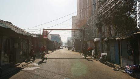 A street view of a once bustling market street after buildings on one side were demolished by authorities. Remaining stores prepare to shut down.