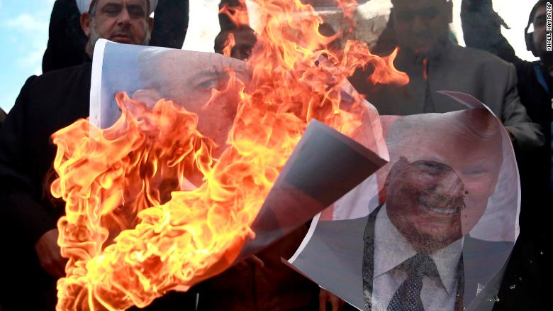 Palestinians burn posters of Israeli Prime Minister Benjamin Netanyahu and US President Donald Trump in Gaza on Thursday.