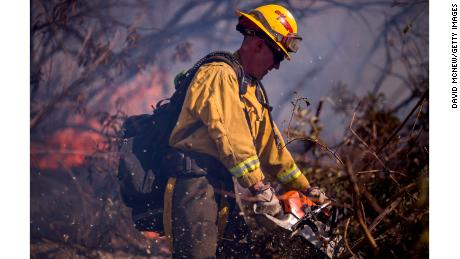 A firefighter cuts brush at the Thomas Fire on December 7, 2017, near Fillmore, California.