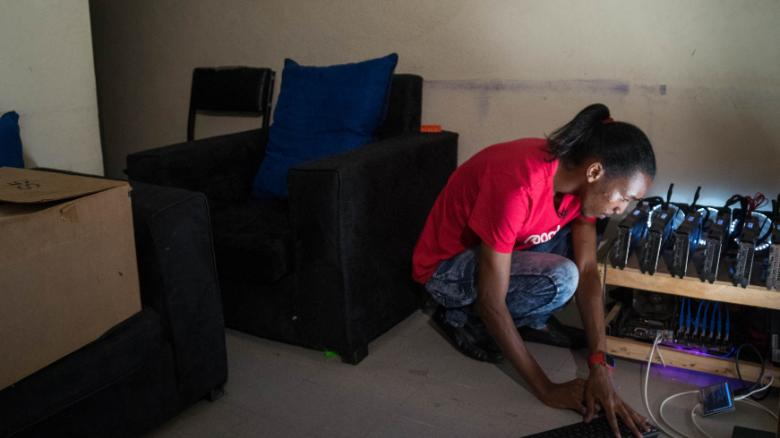 Eugene Mutai in his front room with his self-built cryptocurrency mining machine.