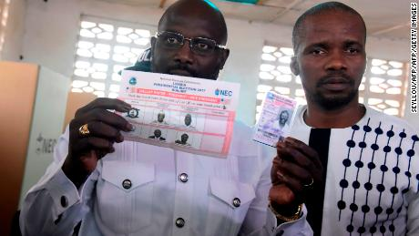 Football icon and Coalition for Democratic Change (CDC) party candidate George Weah presents his voting ballot and identification card for the second round of presidential elections on December 26, 2017 at a polling station in Monrovia.