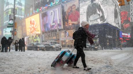 Rebecca Hollis of New Zealand drags her suitcases in a snowstorm through Times Square on her way to a hotel, Thursday, Jan. 4, 2018, in New York. A massive winter storm swept from the Carolinas to Maine on Thursday, dumping snow along the coast and bringing strong winds that will usher in possible record-breaking cold. (AP Photo/Mary Altaffer)
