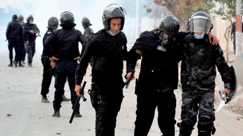 A wounded riot police officer is evacuated during anti-government protests in Tebourba, south of Tunis, on Tuesday.