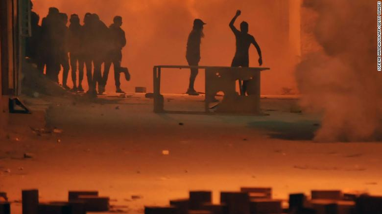 Protesters throw stones towards security forces in Tunis' Djebel Lahmer district early on Wednesday.