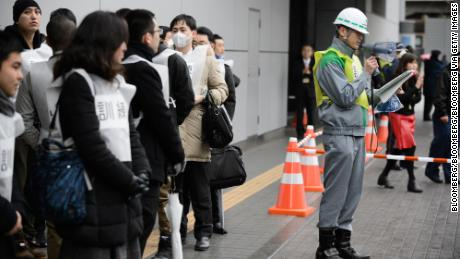 Participants stand outside a subway entrance as a worker with the Tokyo Metropolitan Government gives directions before the start of Monday's missile-attack drill in Tokyo.