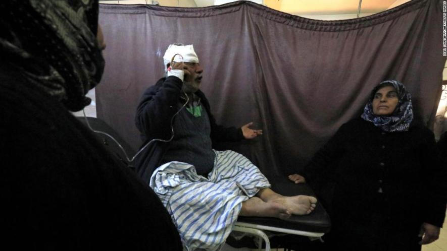 A wounded Kurdish man talks on the phone at the hospital.