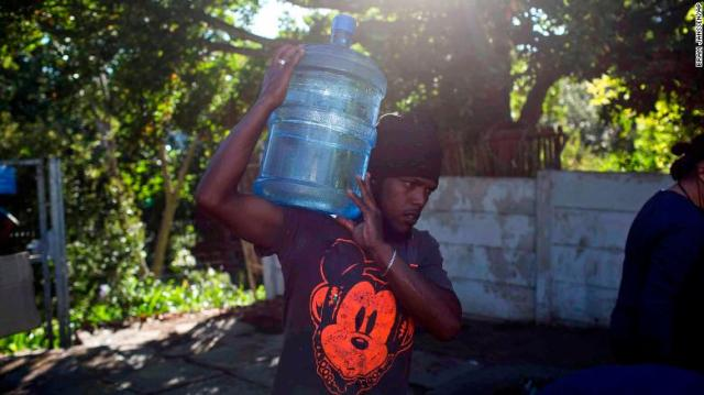 A man carries water at a source for natural spring water in Cape Town on Thursday.