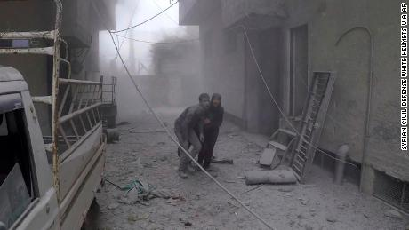 In a White Helmets photo, two civilians flee after airstrikes Monday in a rebel-held Damascus suburb.