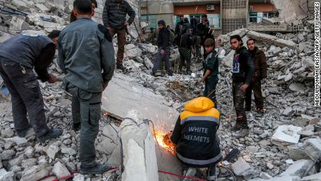 White Helmet volunteers and other civilians clear rubble from a collapsed building airstrikes in Arbin, Eastern Ghouta, on Tuesday.