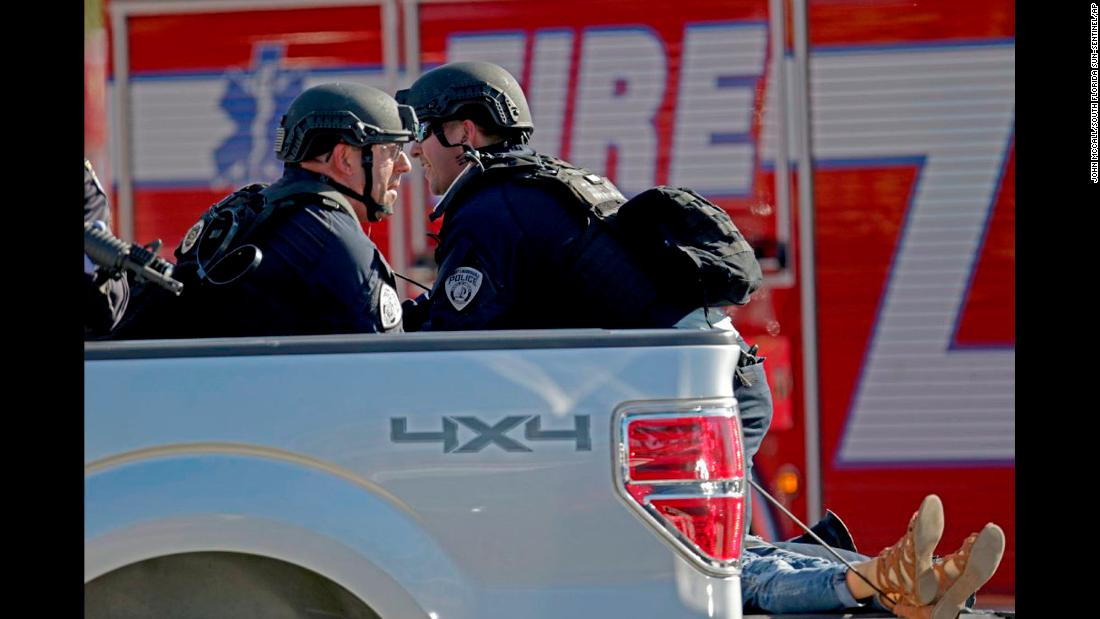 Police officers ride in the back of a pickup truck as they tend to a victim.