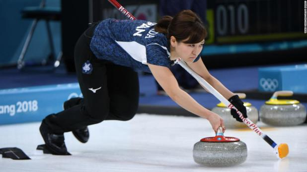 Japan's Chinami Yoshida throws a stone during a curling match against Canada.
