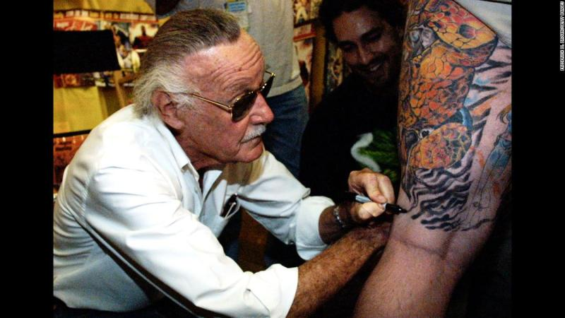 Lee autographs a man's leg during a book premiere in 2001.
