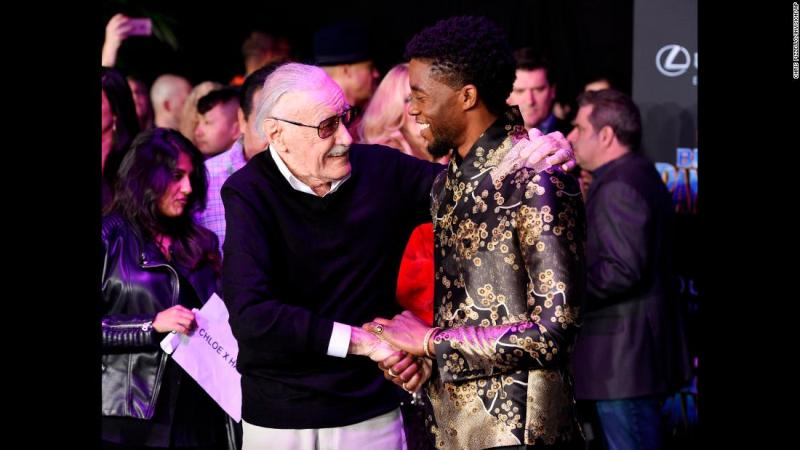 "Lee shakes hands with ""Black Panther"" star Chadwick Boseman at the film's premiere in January 2018."