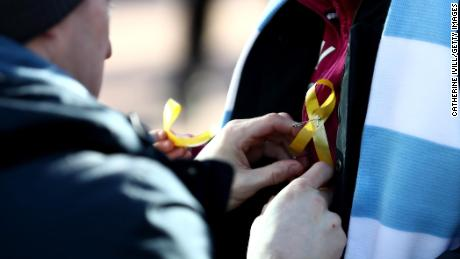 Fans wear a yellow ribbon in support of Pep Guardiola during the Carabao Cup Final between Arsenal and Manchester City at Wembley Stadium.