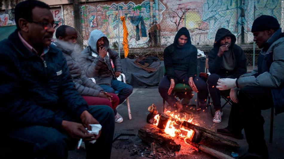 I migranti si riscaldano attorno al fuoco in un campo improvvisato a Roma a febbraio.