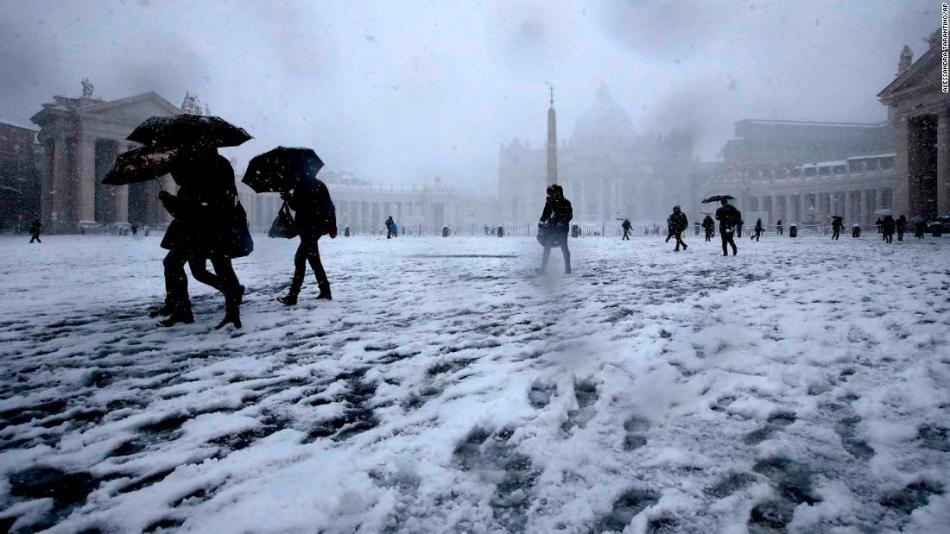 I romani camminano nella neve in Piazza San Pietro il lunedì.