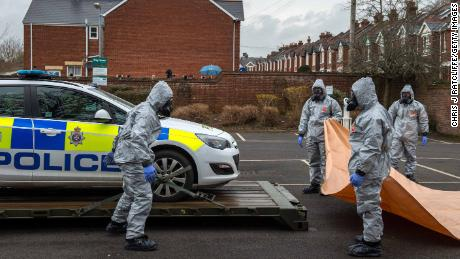 Military personnel in protective suits remove a police car and other vehicles from a public park park as they investigate the poisoning of Sergei Skripal on March 11 in Salisbury, England.