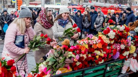People lay flowers for the victims of a fire in a multi-story shopping center in the Siberian city of Kemerovo, about 3,000 kilometers (1,900 miles) east of Moscow, Russia, Monday, March 26, 2018.