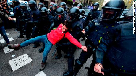 A protester is pulled by riot police blocking the road leading to the central government in Barcelona on March 25, 2018.