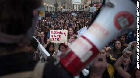 """A woman holds a placard reading, """"Sister, I believe you,"""" as large crowds demonstrate in Málaga."""