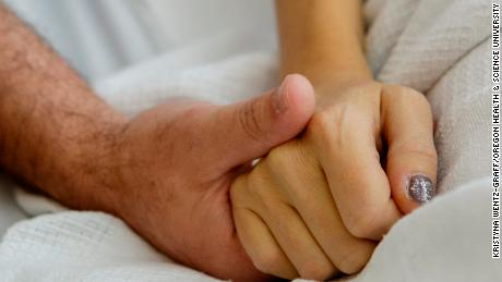 Erika Zak and her husband, Scott Powers, lock hands during a recent hospital visit. The two met 20 years ago.