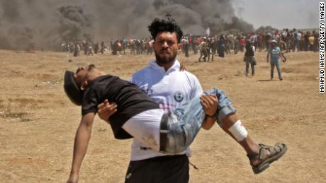 A Palestinian carries an injured man during protests near the border between the Gaza strip and Israel on May 14, 2018.