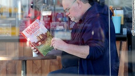 "Thomas Markle reading a book titled ""Images of Britain,"" in an allegedly staged photo."