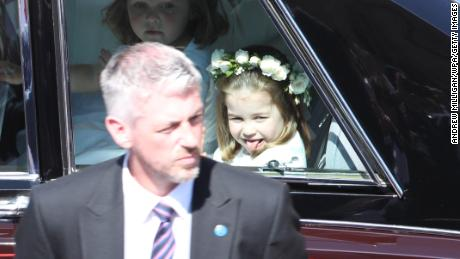 Princess Charlotte, sticking out her tongue, arrives at the wedding ceremony.