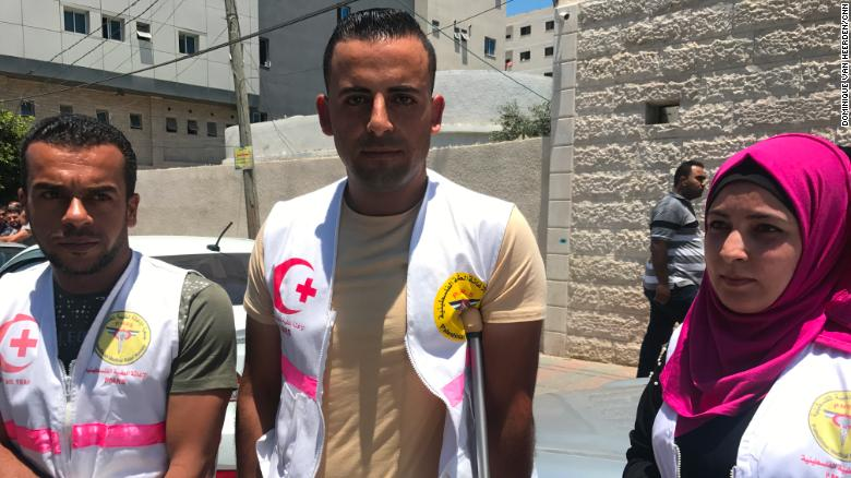 Rami Abu Jazzar, middle, and Rasha Qudeih, right, stand alongside other medical workers protesting outside a UN office in Gaza City.