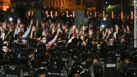Jordanian protesters raise their hands during a demonstration outside the Prime Minister's office.