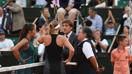 Caroline Wozniacki (right) and Daria Kasatkina talk to French Open officials as light faded in Paris.